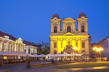 Roman Catholic Cathedral  and outdoor cafes in Piata Unirii at dusk, Timisoara, Banat, Romania, Europe
