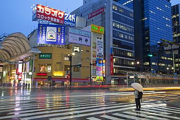 Person waiting to cross street at Hondori shopping arcade at dusk, Hiroshima, Hiroshima Prefecture, Japan, Asia