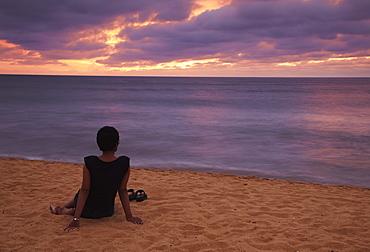 Woman sitting on beach at sunset, Negombo, Sri Lanka, Asia