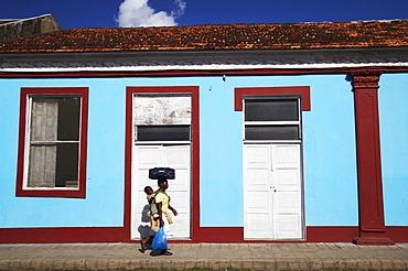 Woman walking past colourful house, Inhambane, Mozambique, Africa