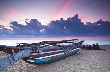 Oruwa (outrigger canoe) on beach at sunset, Negombo, North Western Province, Sri Lanka, Asia