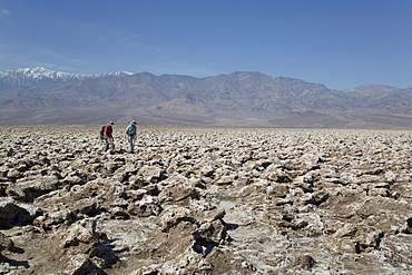 Tourists inspecting the large halite salt crystal formations, Devils Golf Course, Death Valley National Park, California, United States of America, North America