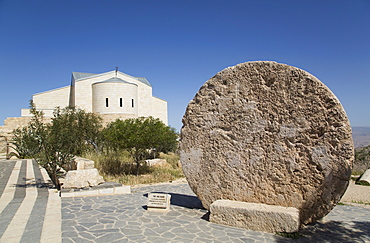 Abu Badd, a rolling stone used to fortify a door, Moses Memorial Church in the background, Mount Nebo, Jordan, Middle East