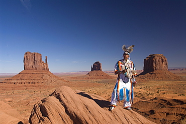 Navajo man in traditional costume, with Merrick Butte on the right, East Mitten in the center and West Mitten Butte on the left in the background, Monument Valley Navajo Tribal Park, Utah, United States of America, North America