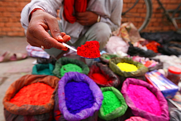 A dye trader offers his brightly coloured wares in a roadside stall in Kathmandu, Nepal, Asia