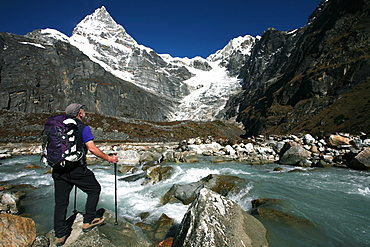 A trekker pauses for a break on the edge of a glacial stream on the way to Mera Peak, a popular trekking peak in the Khumbu Region, near Mount Everest, Nepal, Himalayas, Asia
