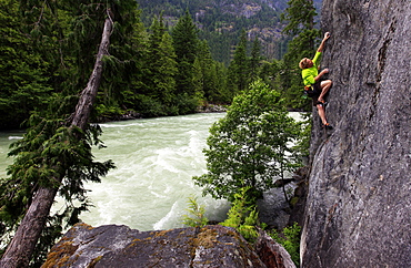 A climber scales riverside cliffs above the Green River, Whistler, British Columbia, Canada, North America