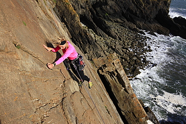 A climber scales cliffs at Baggy Point, Devon, England, United Kingdom, Europe