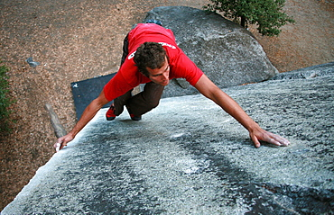 A climber bouldering on the large granite boulders near Camp 4, the National Park Service campground underneath El Capitan, Yosemite Valley, California, United States of America, North America