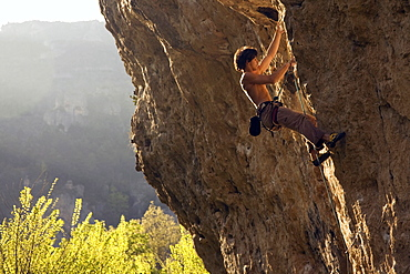 A climber tackles a very difficult route on the rock known as Dromadaire (The Dromedary) by the Tarn river, Gorges du Tarn, near Millau and Rodez, Massif Central, south west France, Europe