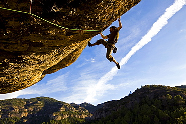A climber tackles an exceptionally difficult, F8c graded, route on a big overhang at the cliffs of Margalef, underneath Montsant, near Lleida and Tarragona, Catalunya, Spain, Europe