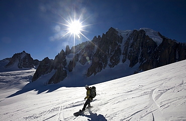 A snowboarder enjoys superb spring snow high on the famous Valley Blanche ski run, one of the world's most celebrated glacier descents, with Mont Blanc Du Tacul in the distance, Mont Blanc, Chamonix, western Alps, France, Europe