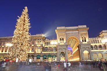 Christmas tree and Galleria Vittorio Emanuele entrance illuminated at dusk, Milan, Lombardy, Italy, Europe