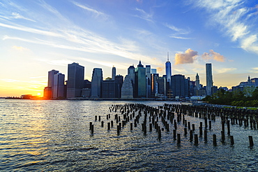 Lower Manhattan skyline at sunset, the remains of old warehouse pilings in the foreground, New York, United States of America, North America