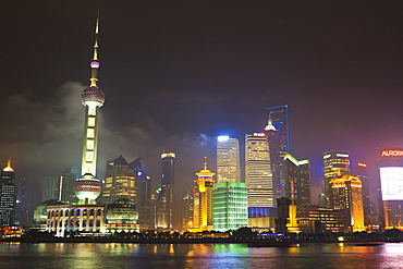 Pudong skyline at night across the Huangpu River, Oriental Pearl tower on left, Shanghai, China, Asia