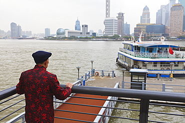 A man watching ferries crossing the Huangpu River, Shanghai, China, Asia