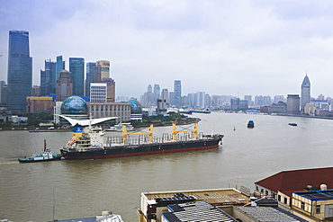 Large transport ship and tug on the Huangpu River that runs through Shanghai, China, Asia