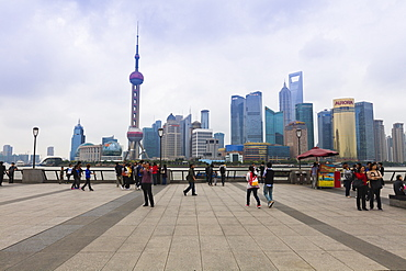 Pedestrians and tourists on the Bund, the futuristic skyline of Pudong across the Huangpu River beyond, Shanghai, China, Asia
