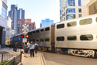 Metra Train passing pedestrians at an open railroad crossing, Downtown, Chicago, Illinois, United States of America, North America