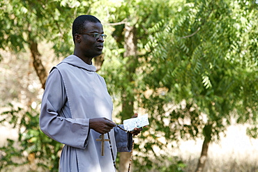 Catholic friar holding rosary and prayer book, Popenguine, Thies, Senegal, West Africa, Africa