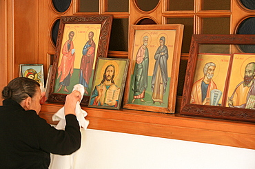 Greek Orthodox woman cleaning icons, Thessaloniki, Macedonia, Greece, Europe