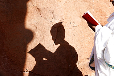 Pilgrim reading outside a Lalibela church, Lalibela, Wollo, Ethiopia, Africa