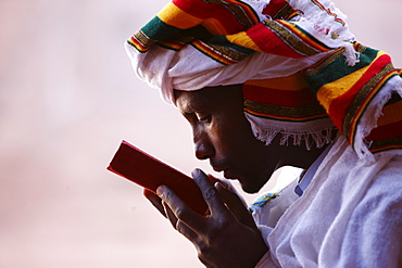 Faithful kissing a Bible outside a church in Lalibela, Ethiopia, Africa