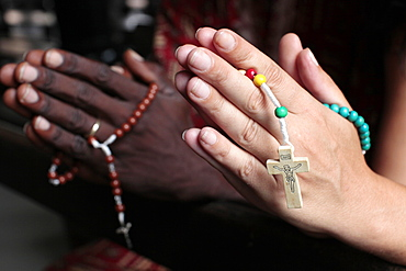 Man and woman praying together with rosaries in a church, Cotonou, Benin, West Africa, Africa