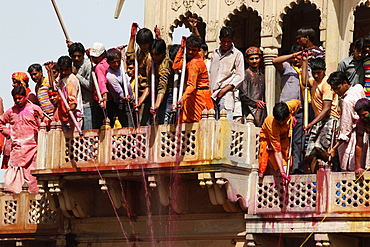 Young men celebrating Holi festival by splashing colored fluids on temple visitors, Nandgaon, Uttar Pradesh, India, Asia