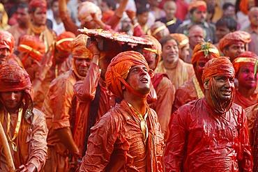 Barsana villagers celebrating Holi in Nandgaon, taunting Nandgaon villagers who throw colored fluids over them, Nandgaon, Uttar Pradesh, India, Asia