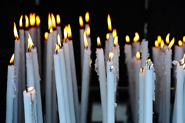 Altar candles in the Cave where Bernadette Soubirous had her Marian apparitions of our Lady of Lourdes in the French town of Lourdes, Hautes-Pyrenees, France, Europe