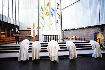 Priests leaning forward during Catholic Mass, Paris, France, Europe
