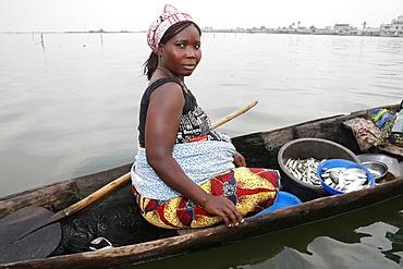 Fish seller on boat, Ayimlonfide-Ladji, Cotonou, Benin, West Africa, Africa