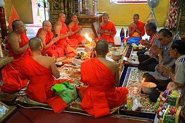 Buddhist monks praying, Sai Sin, the cotton thread symbolizing the sacred bond, Wat Simuong (Wat Si Muang), Vientiane, Laos, Indochina, Southeast Asia, Asia