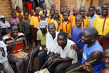 Ugandan villagers drinking home-brewed beer and schoolchildren, Bweyale, Uganda, Africa
