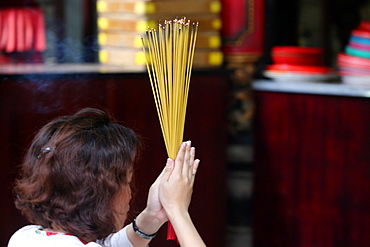 Worshipper burning incense sticks, Taoist temple, Phuoc An Hoi Quan Pagoda, Ho Chi Minh City, Vietnam, Indochina, Southeast Asia, Asia