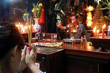 Buddhist worshipper burning incense sticks, Taoist temple, Jade Emperor pagoda (Chua Phuoc Hai), Ho Chi Minh City, Vietnam, Indochina, Southeast Asia, Asia