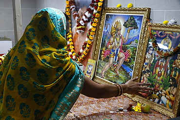 Faithful touching pictures of deities, Shree Ram Mandir, Leicester, Leicestershire, England, United Kingdom, Europe