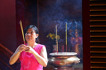 Buddhist worshipper with incense sticks, Khanh Van Nam Vien Taoist pagoda, Ho Chi Minh City, Vietnam, Indochina, Southeast Asia, Asia