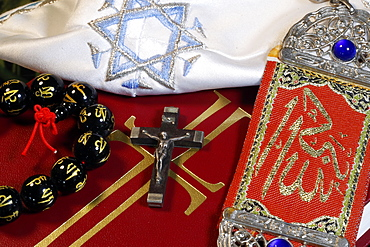 Christianity, Buddhism, Islam and Judaism, interfaith symbols of Bible, crucifix, Kippah, Allah monogram and Mala, Haute-Savoie, France, Europe