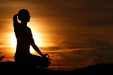 Silhouette of a woman in lotus position, practising yoga against the light of the evening sun, French Alps, France, Europe