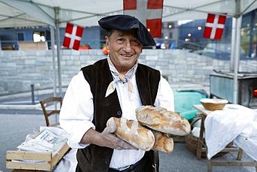 Baker with artisan bread, the agriculture fair (Comice Agricole) of Saint-Gervais-les-Bains, Haute Savoie, France, Europe