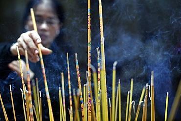 Mariamman Hindu Temple, woman burning incense sticks, Ho Chi Minh City. Vietnam, Indochina, Southeast Asia, Asia