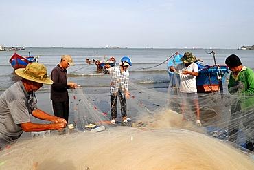 Fishermen repairing fishing nets at Tam Duong beach, Vung Tau, Vietnam, Indochina, Southeast Asia, Asia