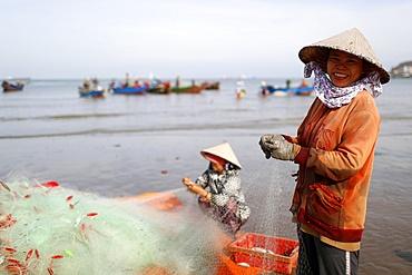 Fishermen and women repairing fishing nets at Tam Duong beach, Vung Tau, Vietnam, Indochina, Southeast Asia, Asia
