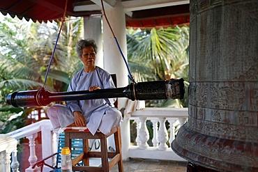 Buddhist worshipper rings bell, Phuoc Thanh Buddhist pagoda, Cai Be, Vietnam, Indochina, Southeast Asia, Asia