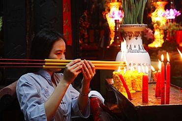 Vietnamese woman praying with incense sticks, The Jade Emperor Pagoda, Ho Chi Minh City (Saigon), Vietnam, Indochina, Southeast Asia, Asia