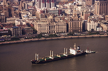 Bund and cargo ship on the Huangpu River, Shanghai, China, Asia