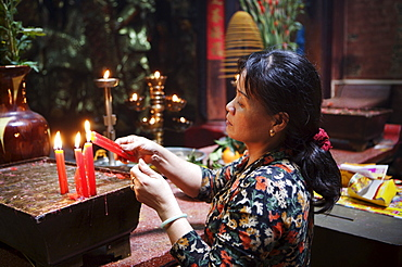 Local woman making an offering in a Buddhist temple, Ho Chi Minh City, Vietnam, Indochina, Southeast Asia, Asia
