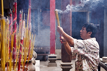 Local man making an offering in a Buddhist temple, Ho Chi Min City, Vietnam, Indochina, Southeast Asia, Asia